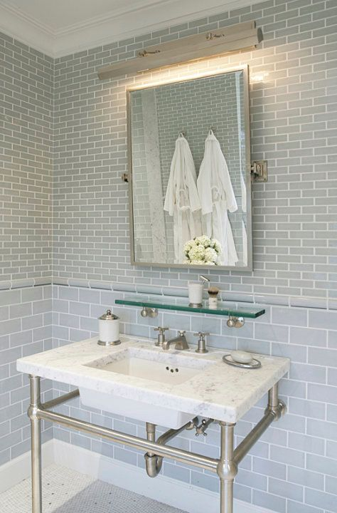 source: Mabley Handler  Amazing bathroom with blue glass subway tiles backsplash, polished nickel picture light, rectangular pivot mirror, vintage glass shelf and marble top 2-leg washstand.