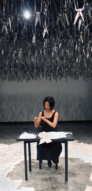 The hovering mass of the downward-pointed scissors represent the distant fear and looming violence present in today's cultural climate. The sharp blades above the artist are put in contrast by the silent and simple act of mending. The dichotomous result of the instant fear superimposed with the calming effect of the sewing created a surreal atmosphere in the room.""