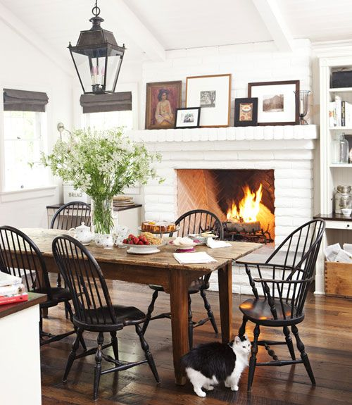 One of the coziest dining rooms I've seen of late. Love the fireplace, the layering of the pictures above it, the windsor chairs in black and those luscious floors (why cover them with a rug?).