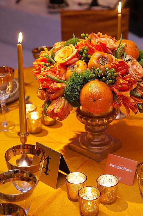 This low arrangement features parrot tulips, oranges, persimmons and roses in a ...
