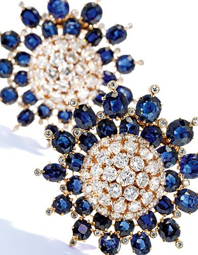 A Pair of 18 Karat Gold, Sapphire and Diamond Brooches, Van Cleef & Arpels. Designed as two flowerheads, the petals composed of round, oval and cushion-cut sapphires weighing approximately 20.00 carats, accented by numerous round and cushion-cut diamonds weighing approximately 9.80 carats Estimate $25/35,000. Photo: Sotheby's
