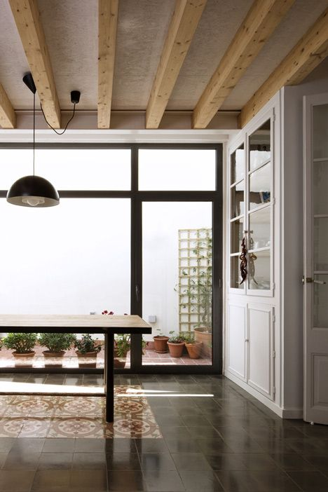 Here's a renovated early twentieth-century house in Barcelona featuring a mixture of old and new tiles
