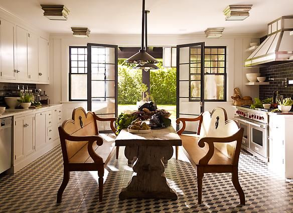 white cabinets and black subway tile  benches and trellis table  black trim windows and doors