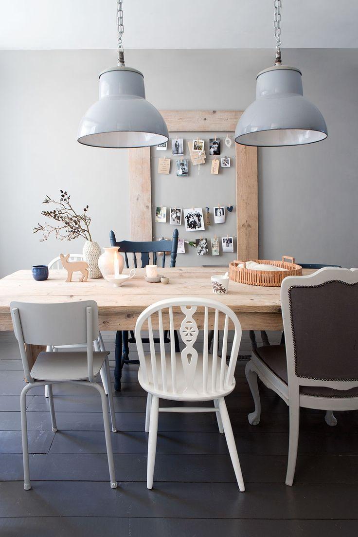 Houten tafel met stoelen in verschillende vormen en kleuren voor een speels effect. In deze keuken mag worden geleefd.