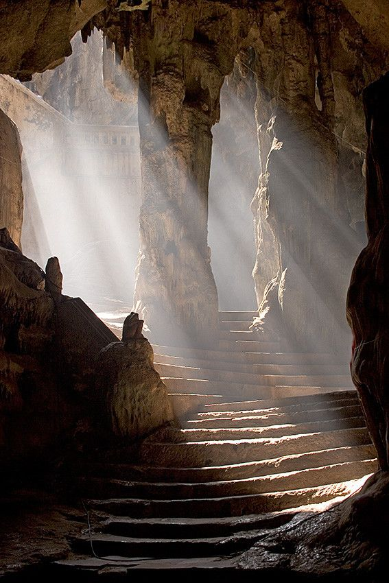Rays of Light by Craig Ferguson. Sun shining into the entrance to the Khao Luang Cave temple, Phetchaburi, Thailand.