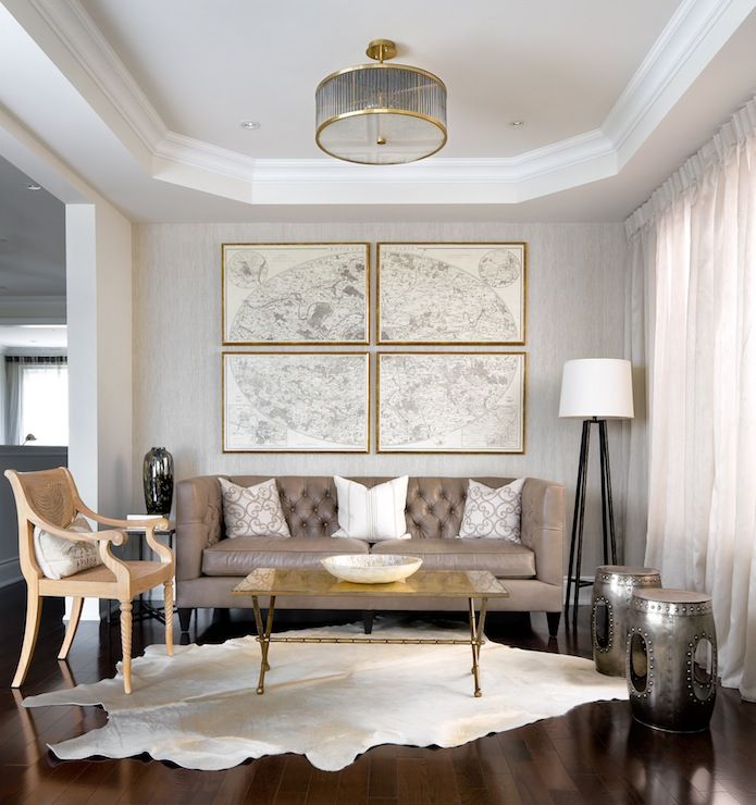 Amazing living room with octagonal recessed ceiling and recessed lighting. Gray textured walls paired with floor to ceiling gray sheer window panels. Set of vintage maps framed in gold frames over gray leather tufted high-back sofa, galvanized metal stools and gold faux bamboo cocktail table over white cowhide rug.