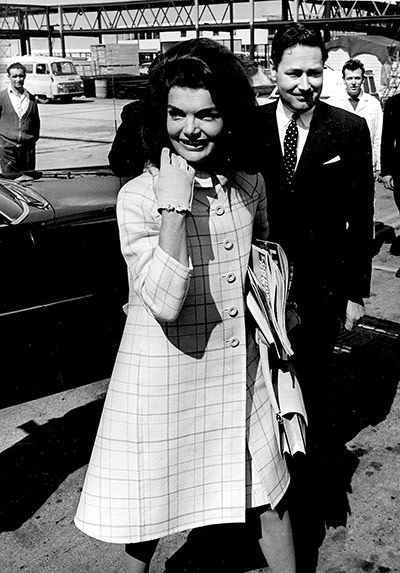 Jackie Kennedy arrives at Heathrow Airport in 1966 and immediately sets the template for first-lady-on-tour chic in a classic Gucci windowpane check coat Photograph: Rex Features/Rex Features