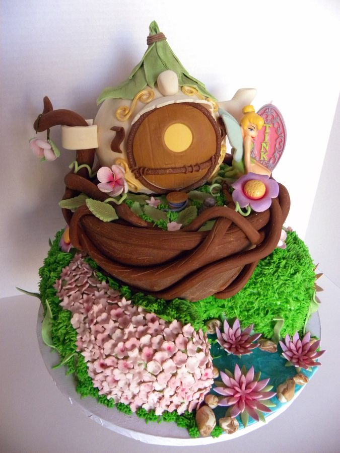 this is prob one of my favorite cakes i have done! everything is edible except tinkerbell candle. teapot made of cake everything made of fondant except buttercream grass. cake is chocolate with cookies and cream filling