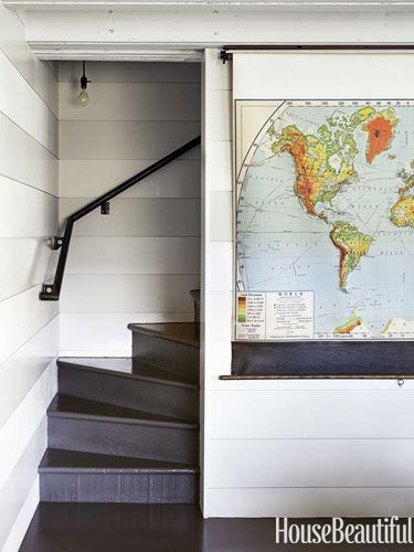 Using a pull-down map to hide the TV. Great idea! Liking the striped walls in this space too. #maps #TV #stripes