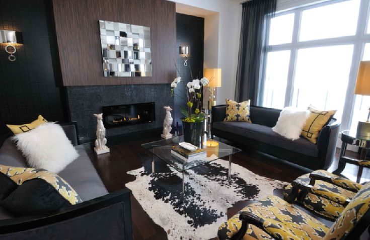 Modern gray black & yellow living room design with modern black glass tiles backsplash, contemporary mirror, white porcelain dog statues, white &black cowhide rug, charcoal gray velvet sofas, barcelona cocktail table, yellow & gray chairs and gray curtains.