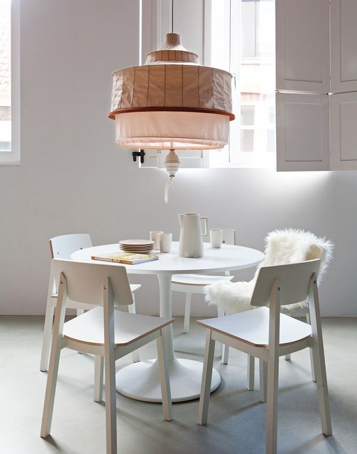 White dining room with round table and lamp with nude colours