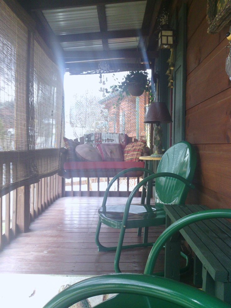 Our little country screen porch...The grands love the swing, we enjoy coffee in our retro green chairs watching the neighbors go by.