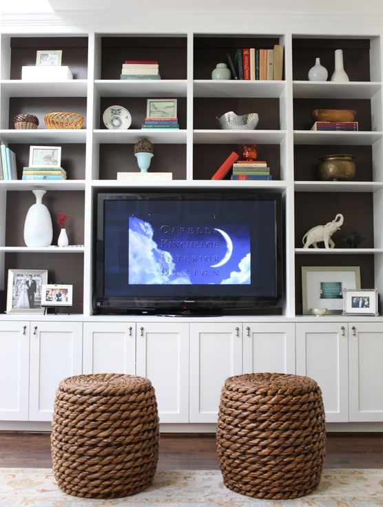 living rooms - rope stools white built-ins TV back shelves lined brown paper  Fantastic white built-ins with backs of shelves lined with brown