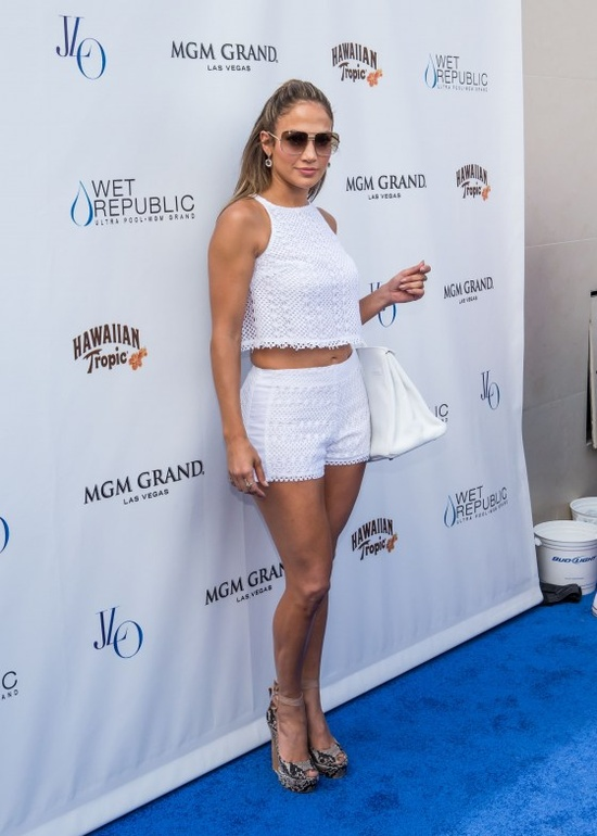 Jennifer Lopez Hosts at Wet Republic Ultra Pool in Las Vegas in a white crochet crop top and matching shorts with python platforms.