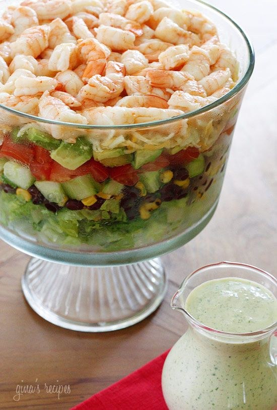 layered summer salad - shrimp, avocados, grilled corn, black bean salsa, cucumbers, tomatoes, cheese, & creamy cilantro tomatillo dressing.