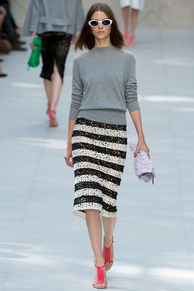 perforated black and white skirt, long sleeve grey sweater, white cat eye shades, pink heels
