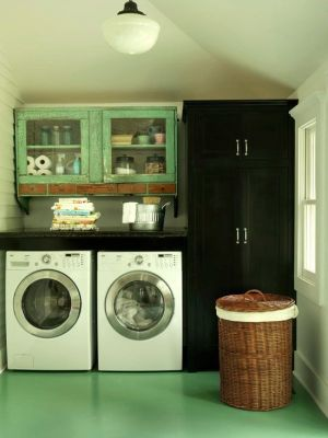 Thrifty Fix -Thrifty solutions resolve storage issues without breaking the bank. A blend of modern appliances and vintage furnishings, such as these distressed wooden cabinets, lend this laundry room an authentic aesthetic. Salvage shops are great places to look for custom pieces to add character to your space.