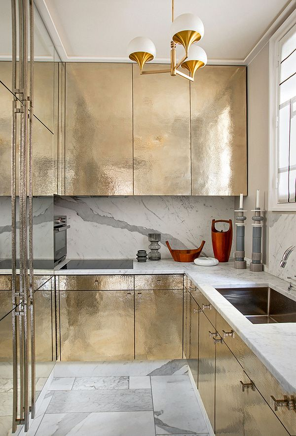 Gold glam kitchen with carrara marble back splash, counter tops, and tiled floor! MCM light fixture to die for. Love how big this small kitchen feels. Gold kitchen by Jean Louis Deniot