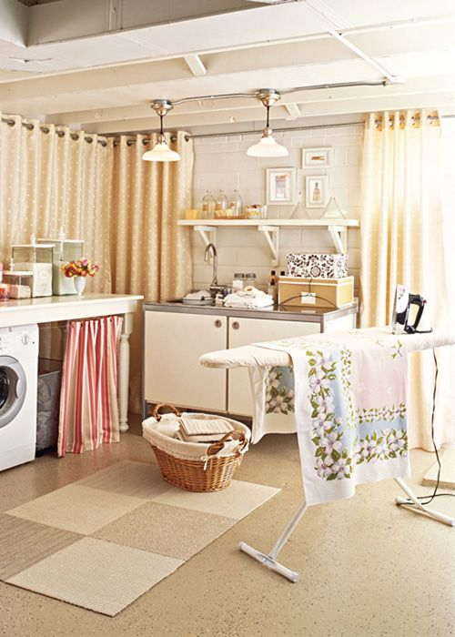 A laundry room can still be warm and cozy - here, the cement walls are hidden behind subtle polka-dot curtains, while other home accessories, such as decorative boxes and glass bottles and the pair of ceiling fixtures, offer homey warmth.
