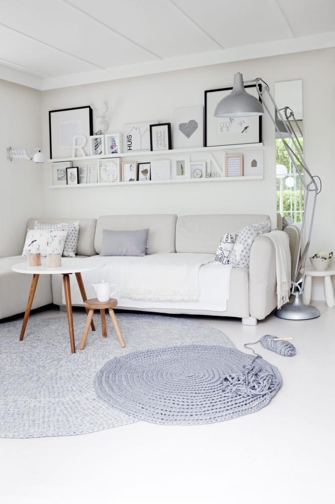 STUE: Delikat stue i hvitt med enkelte grå detaljer og innlag av tre for å myke opp. Over sofaen henger en samling rammer med fotografier og selvlaget kunst. Teppet er heklet av garnet Zpagetti fra Hooked. Det består av tykke, elastiske tøyremser som er lett å jobbe med.