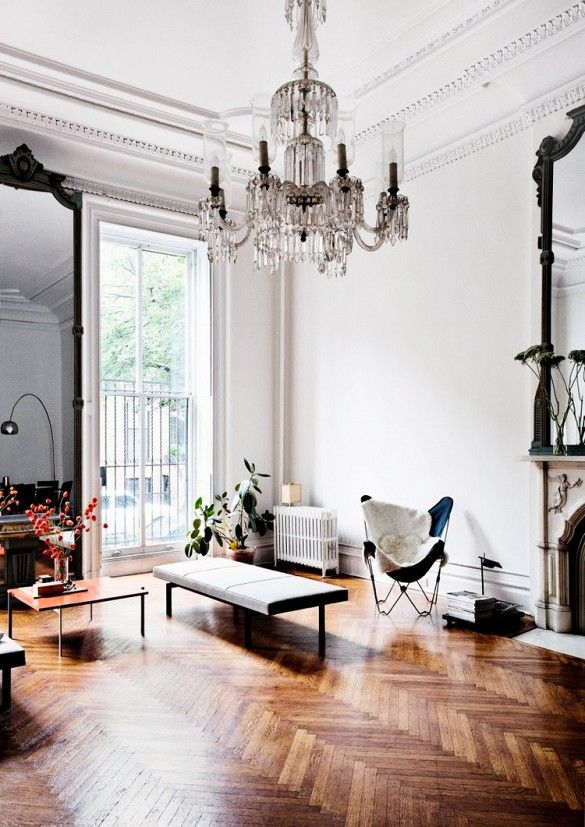 Grand living room with crystal chandelier, full body mirror, and herringbone wood flooring.