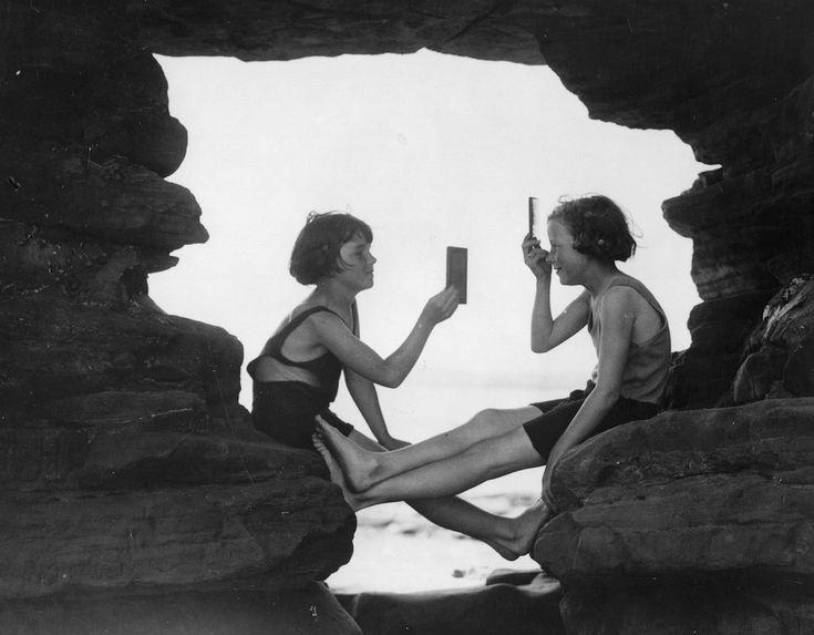IlPost - Amiche al Mare - Una ragazzina Regge Uno specchio MENTRE L'Altra SI Pettina DOPO Una nuotata, in Una grotta affacciata sul mare nel REGNO UNITO, 13 giugno 1935.  (William Vanderson / Fox Photos / Getty Images)