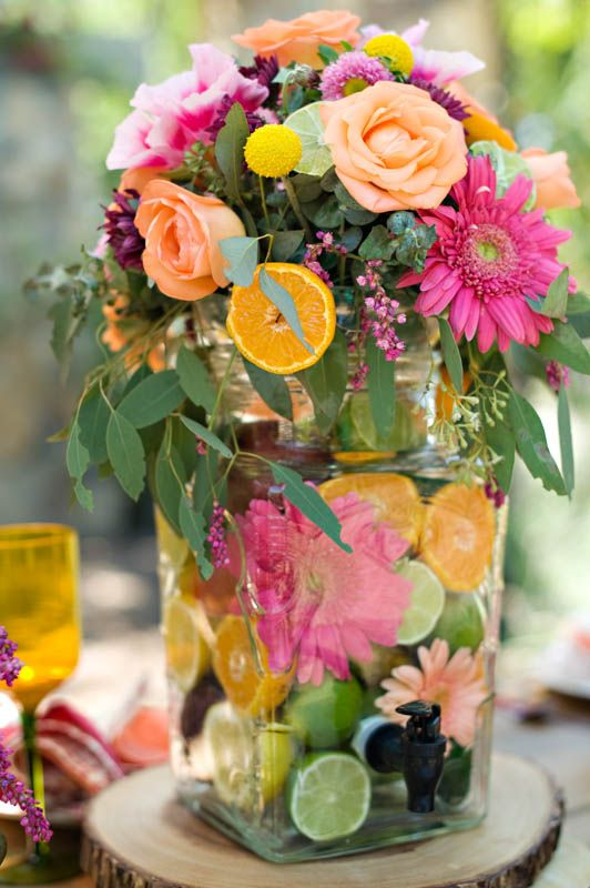 Drink dispenser filled with fruit and topped with flowers as a vase.