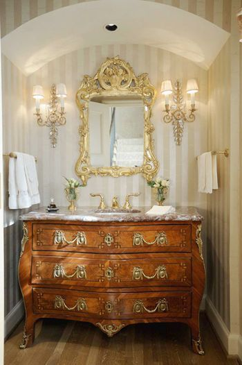 Why not repurpose a beautiful, but not priceless, commode?  A marble top and gold hardware bring incredible warmth to the niche in this bathroom.