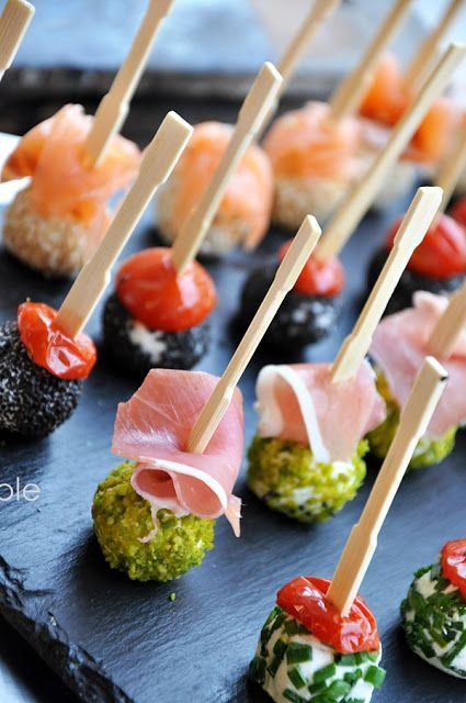 Appetizers : goat cheese rolled in sesame seeds, chives and pistachio topped with smoked salmon, tomato, and prosciutto
