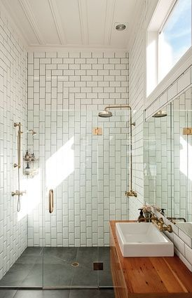 White subway tile installed vertically + horizontally, wood countertop, basin sink, glass shower wall and door, brass fixtures