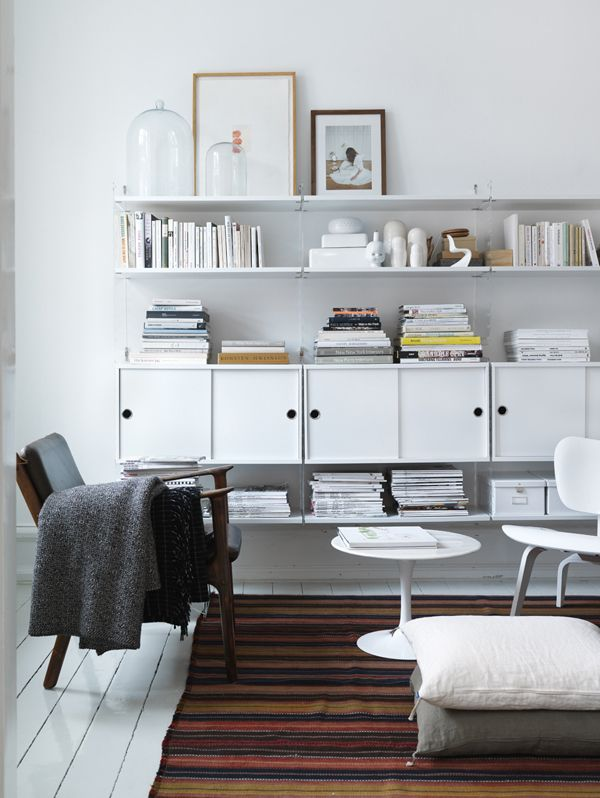 All white bookshelves and accessories give this sitting area a clean aesthetic.
