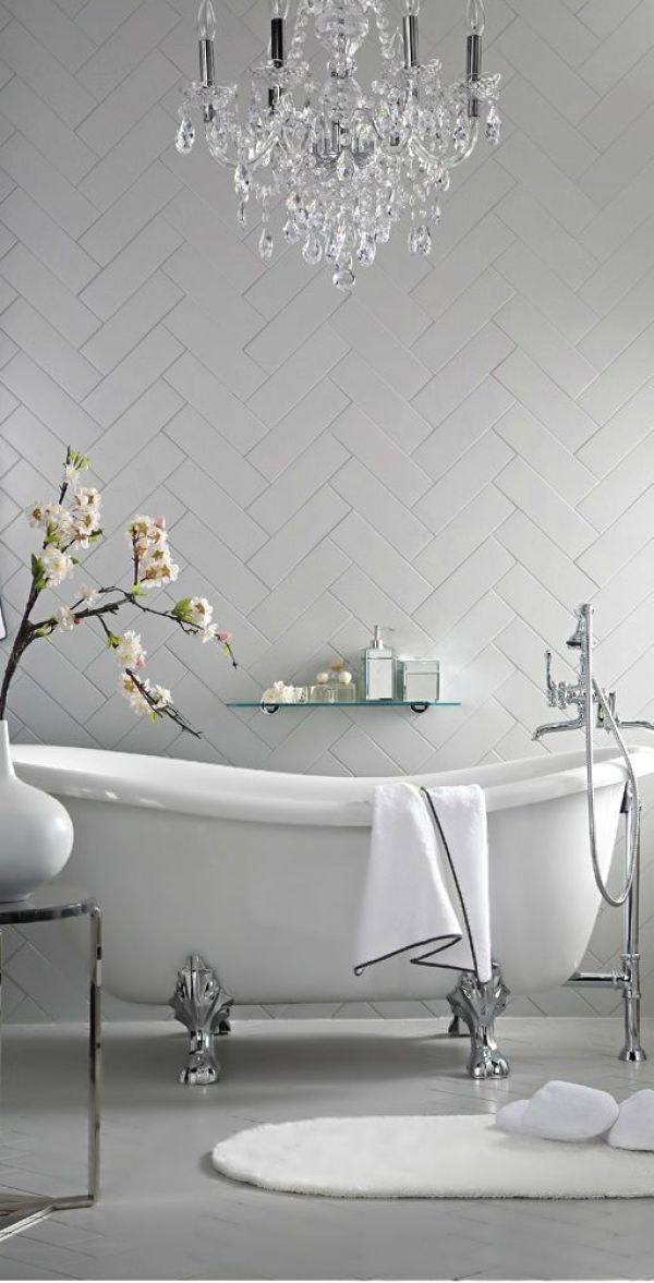 Freestanding bath tub with chandelier and chevron tile