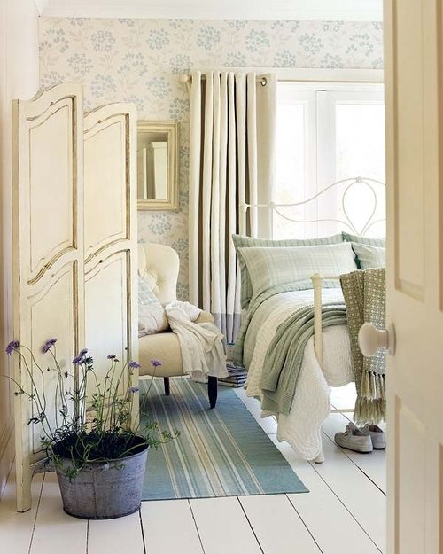 A beautiful cottage style bedroom in shades of...