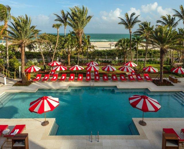 """Piscine d'hôtel avec méridienne rouge et parasols rayés de canne en bonbon rouge et blanc tout autour. """"Width ="""" 1280 """"height ="""" 1036"""