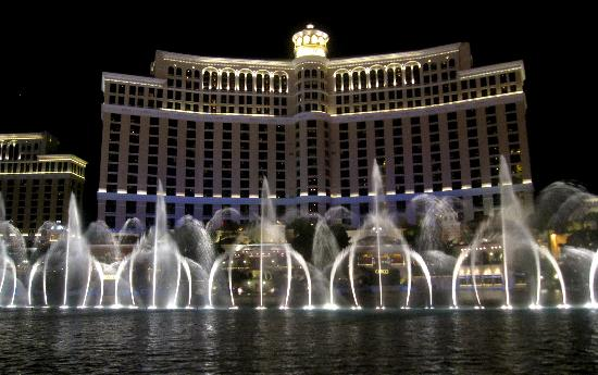 Bellagio fountain show after dark from Strip with hotel in background