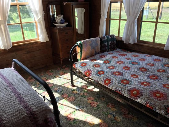 Bedroom in the Johnny Cash Boyhood Home Museum, Arkansas. Shows hand made quilts on and iron bed. This photo of Johnny Cash House is courtesy of TripAdvisor