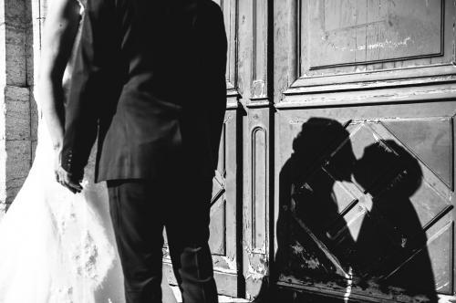 Le baiser des jeunes mariés avec l'ombre sur la porte de l'église