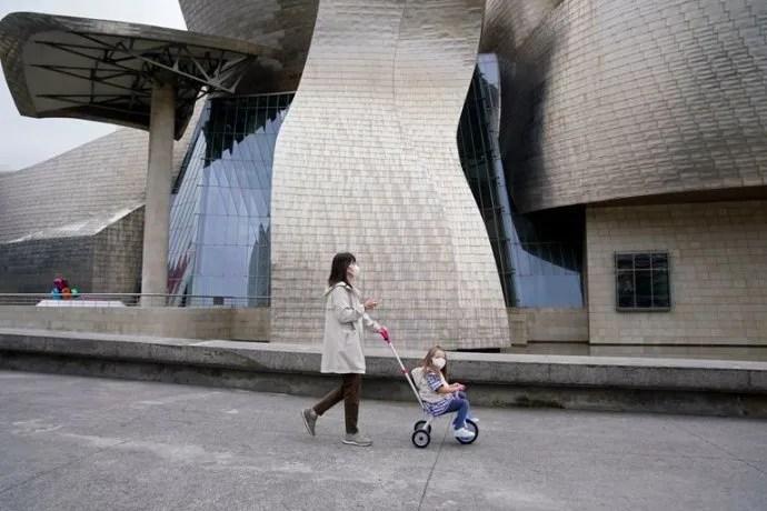 Una madre pasea con su hija en las afueras del Museo Guggenheim en Bilbao.