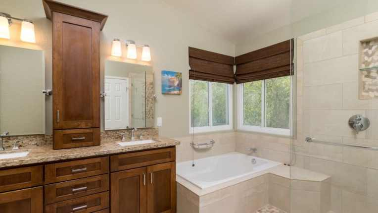 How to Save Money on a Bathroom Remodel   Angie s List remodeled bathroom with cabinets  tile and tub