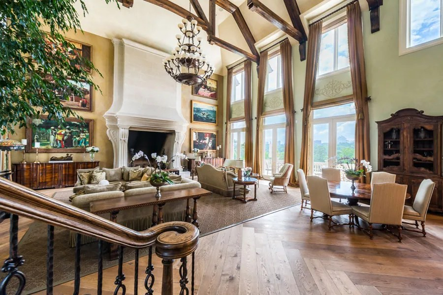 The great room boasts double-height ceilings and a grand fireplace.