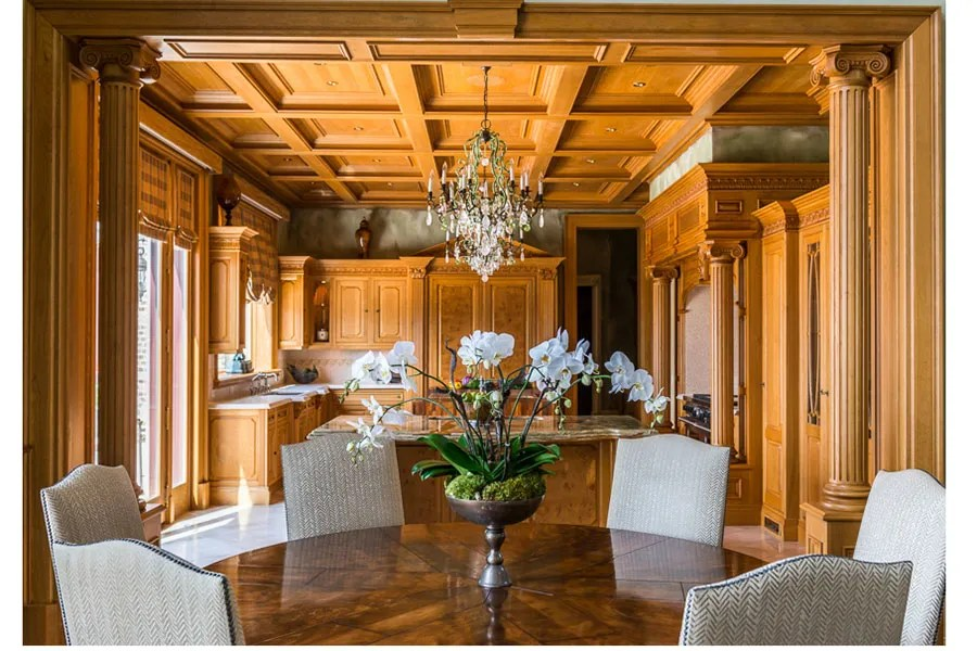 Highlights of the kitchen include coffered ceilings, ornate millwork, and a balcony.