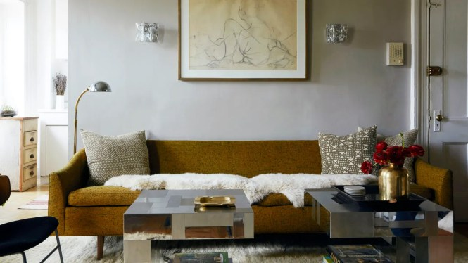 An Abstract Drawing Is Flanked By Twin Sconces Above Olivegreen Couch And Metallic Cubist Coffee