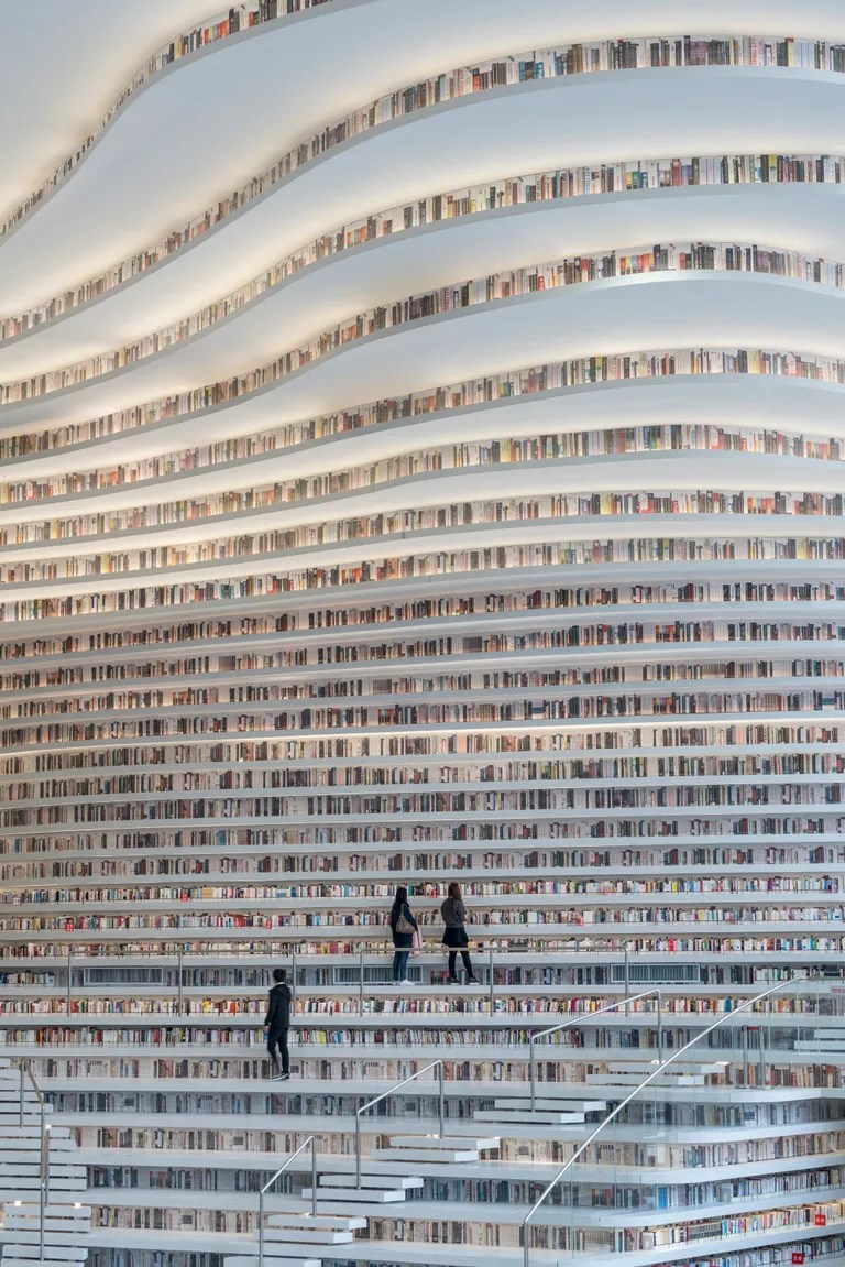 The undulating rows of books allow visitors to walk among various shelves while browsing.