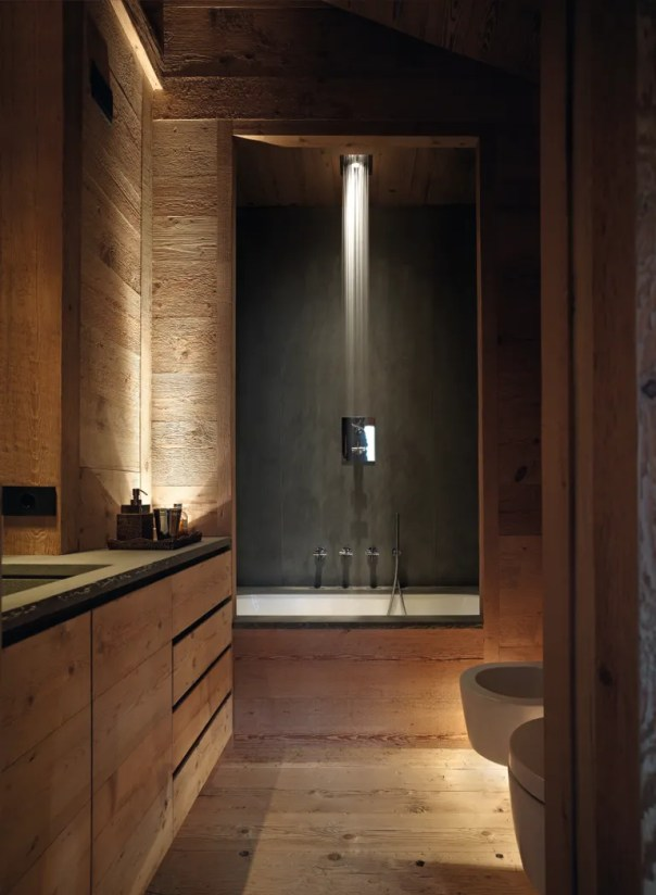 Dramatic lighting and raw wood defines this bathroom in a home in Cortina, Italy.