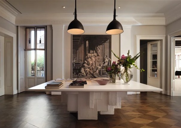 In another Milanese home, traditional elements, like the parquet flooring, pair with contemporary design, noted in the geometric table.