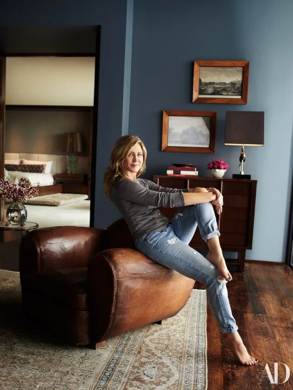 Aniston in her office, with a teal-toned wall and a neutral rug.
