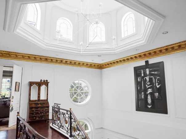 The stair hall features a Julie Neill Designs chandelier, an antique secretary bookcase, and a Mimmo Paladino painting.