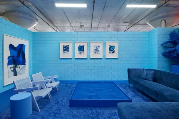 blue room with blue sand box, lounge chairs, sectional, and blue art on the walls