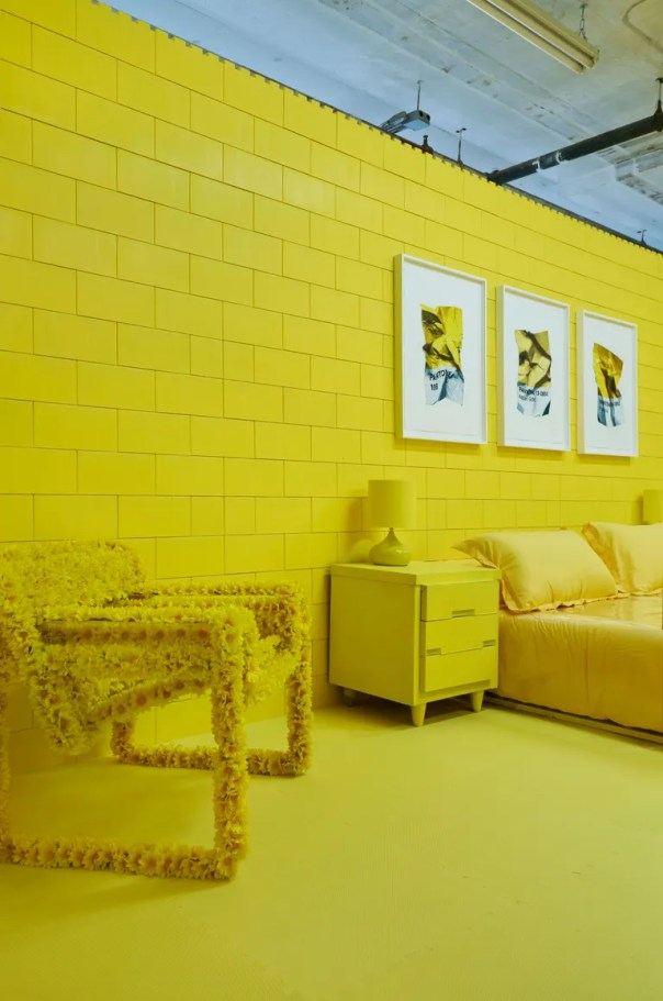 yellow bedroom with three artworks above yellow bed, nightstand, and fuzzy chair