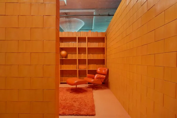 all-orange room with orange shag rug, shelving, and Eames lounger